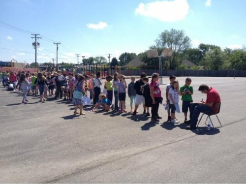 elementary-school-students-line-up-for-a-yearbook-signature-from-the-school-janitor